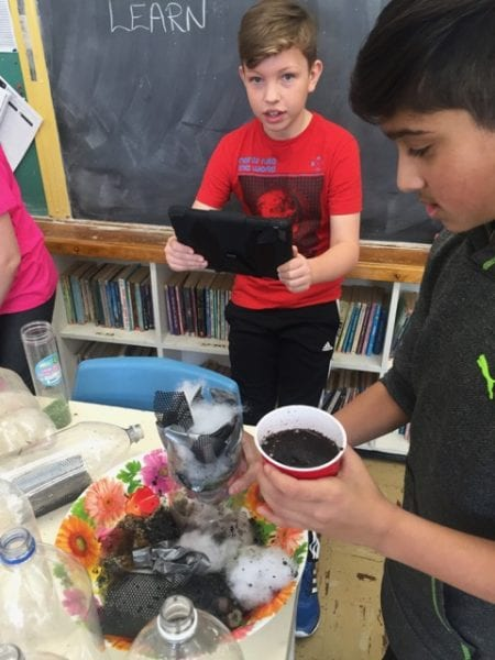 Elementary students building a water filer system with old pop bottles