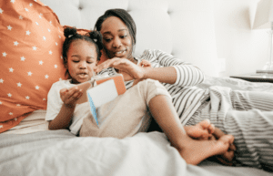 Child and mother look at book in bed