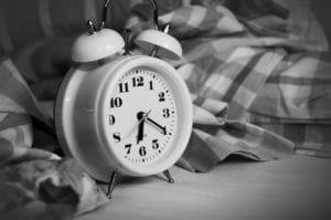 Round alarm clock beside bed