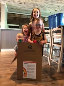 Four smiling kids standing in a delivery box