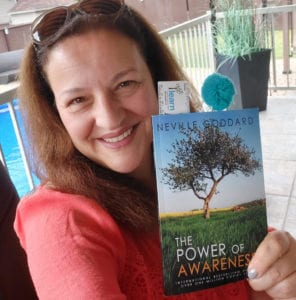 Smiling woman holding book: The Power of Awareness